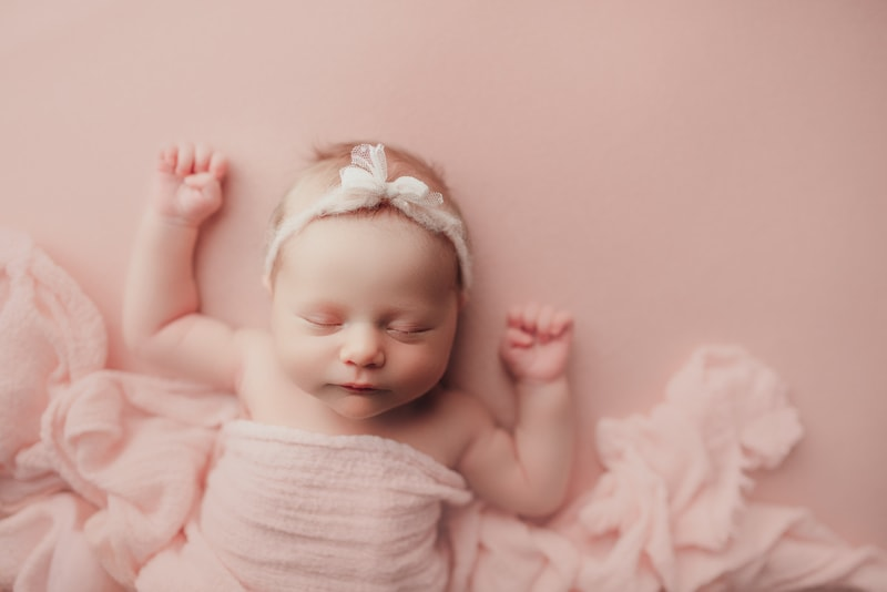 Wellsville NY Family & Newborn Photographer, baby girl sleeping on pink background