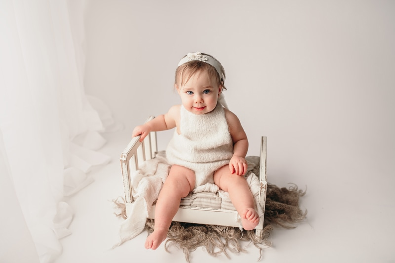 Wellsville NY Family & Newborn Photographer, little girl sitting on miniature white bed