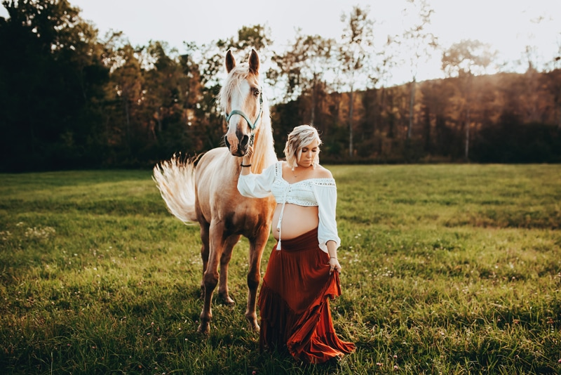 Wellsville NY Family & Newborn Photographer, pregnant woman walking a horse through a grassy area