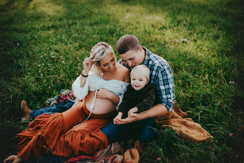 Wellsville NY Family & Newborn Photographer, family of 3 sitting in the grass together
