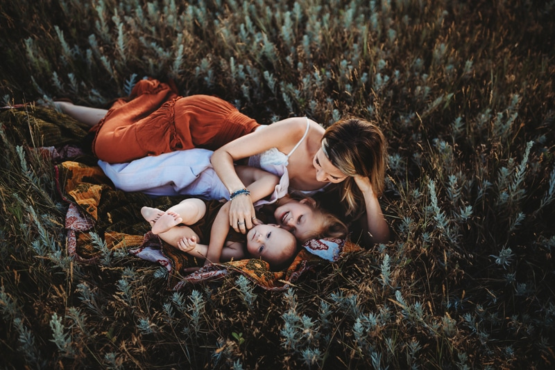 Wellsville NY Family & Newborn Photographer, mother laying in the grass with her two little children