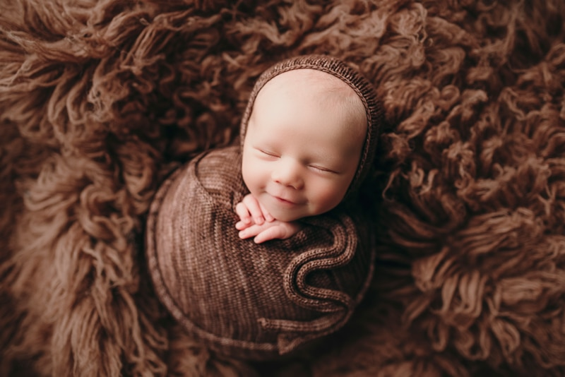 Wellsville NY Family & Newborn Photographer, baby smiling in their sleep all wrapped up in brown material