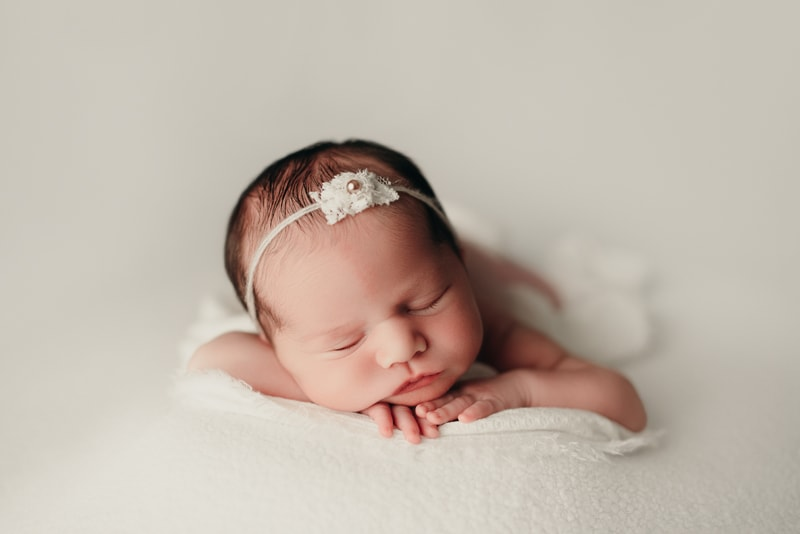 Wellsville NY Family & Newborn Photographer, baby girl asleep on her stomach on cream color backdrop