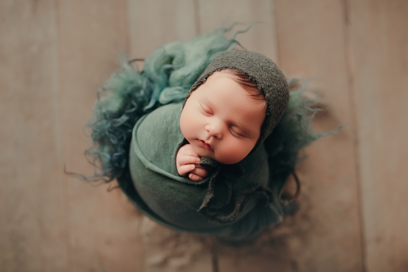 Wellsville NY Family & Newborn Photographer, sleeping baby wrapped up into a bad with green material