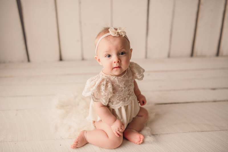 Wellsville NY Family and Newborn Photographer, baby sitting on white wooden floor