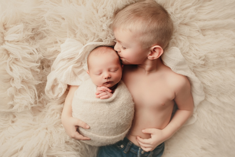 Wellsville NY Family and Newborn Photographer, little brother holding baby brother in swaddle