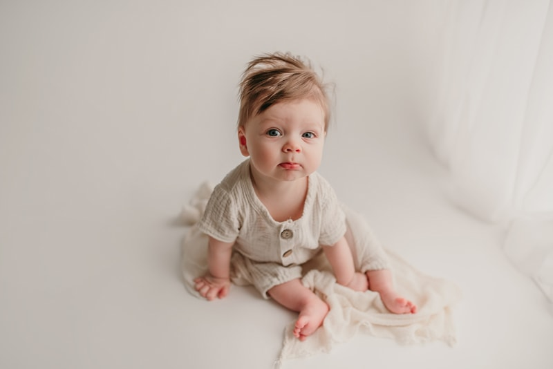 Wellsville NY Family and Newborn Photographer, litte baby sitting up on white backdrop