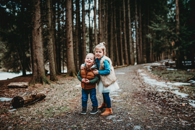 Wellsville NY Family and Newborn Photographer, little brother and sister standing together in forest